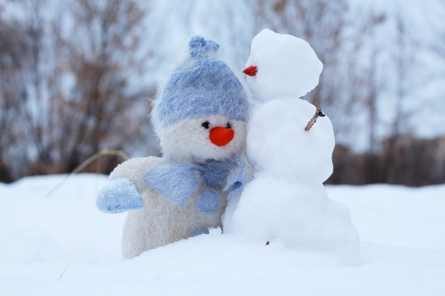 small stuffed snowman next to a small snowman outside